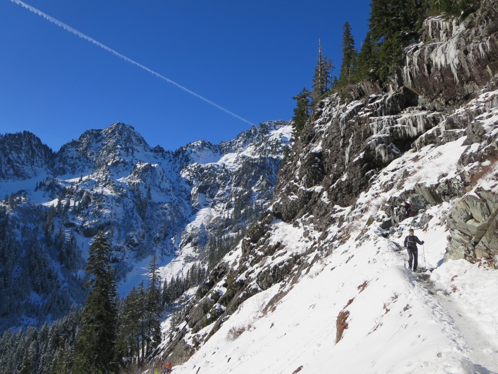 Lone hiker with poles running down a narrow ledge of snow on the side of a mountain under sunny skies.