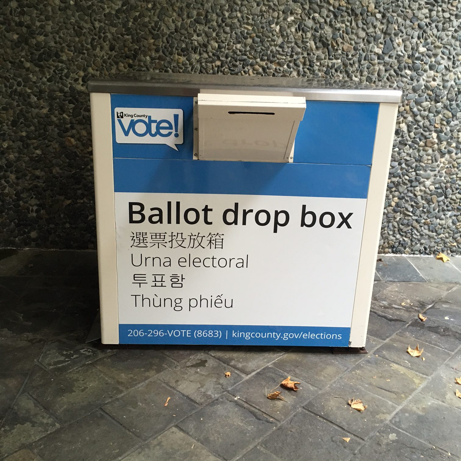 Blue and white box with slit for ballots on a sidewalk.