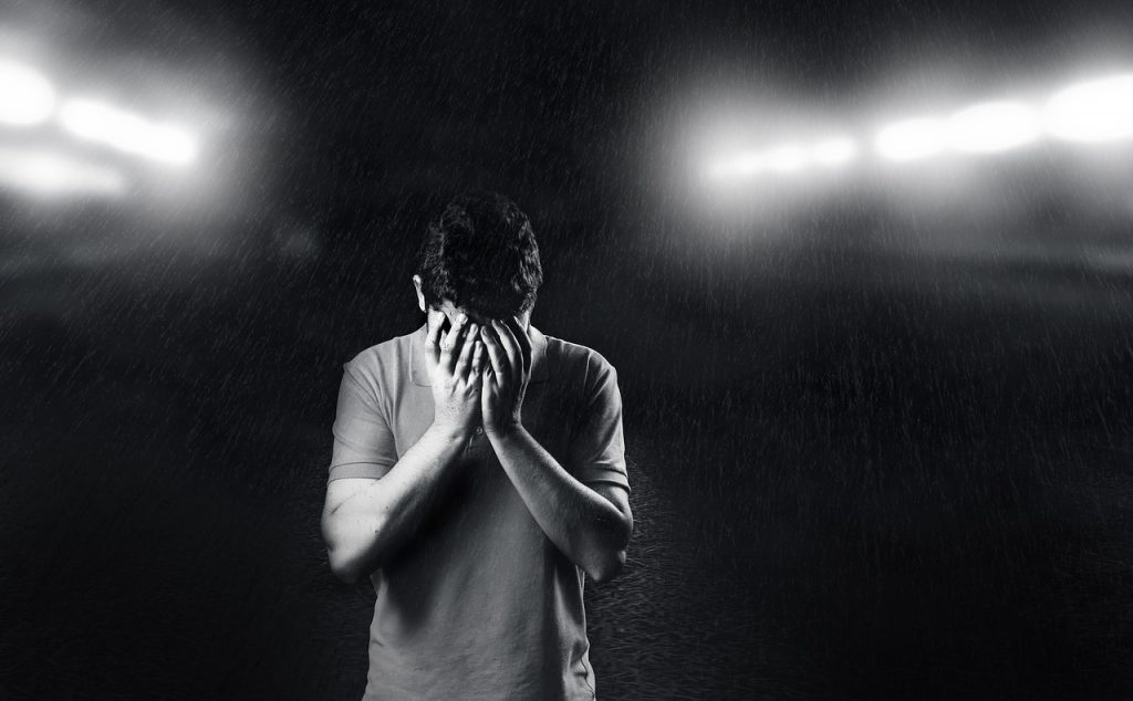 Black and white background, man with head in his hands, crying